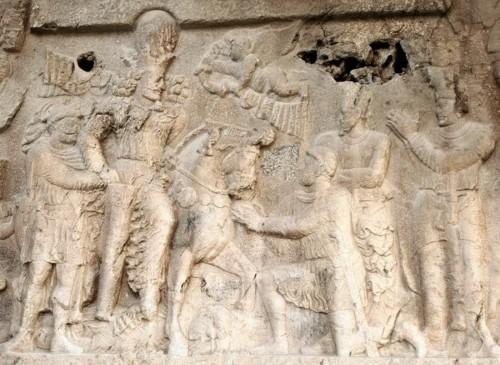 شاپور 3 - امپراتوری روم صفر! نگارهی نمادینی در شهر باستانی بیشاپور (نزدیکی کازرون) از پیروزی شاپور اول، دومین پادشاه ساسانی، بر سه امپراتور روم. بهترتیب اولی که بر زمین و زیر سم اسب شاپور افتاده گوردیان سوم است که در سال ۲۴۳ میلادی به بینالنهرین حمله کرد اما در کنار رود فرات از شاپور شکست خورد و بهدست وی کشته شد. (البته این ادعای شاپور در سنگنبشتههای متعددی است که برجا گذاشته، ولی منابع رومی ادعا میکنند که این امپراتور 19 ساله در اثنای جنگ به مرگ طبیعی یا به توطئهی جانشین خود از دنیا رفت.) دومی که شاپور مچ دستش را فشار میدهد فیلیپ عرب، جانشین گوردیان است که پس از شکست وی ناچار شد با امضای پیمان خفتباری سرزمینهای بسیار و ۵۰۰ هزار دینار طلا بهعنوان غرامت جنگی به ایران بپردازد. سومی هم که زانو زده والرین است که در اواخر سال ۲۵۹ یا اوایل ۲۶۰ در جنگ اِدِسا (در ترکیهی فعلی) از شاپور شکست خورد و بههمراه بسیاری از اشراف و بزرگان و از جمله مهندسان آب و تاسیسات روم اسیر شد. (البته باید این را در نظر داشت که آغاز شاهنشاهی ساسانی در قرن سوم میلادی همزمان با دوران انحطاط امپراتوری روم بود. در این مدت امپراتوران زیادی در آن سرزمین بر تخت مینشستند که پس از چند سال یا حتی چند ماه کشته یا برکنار میشدند.)
